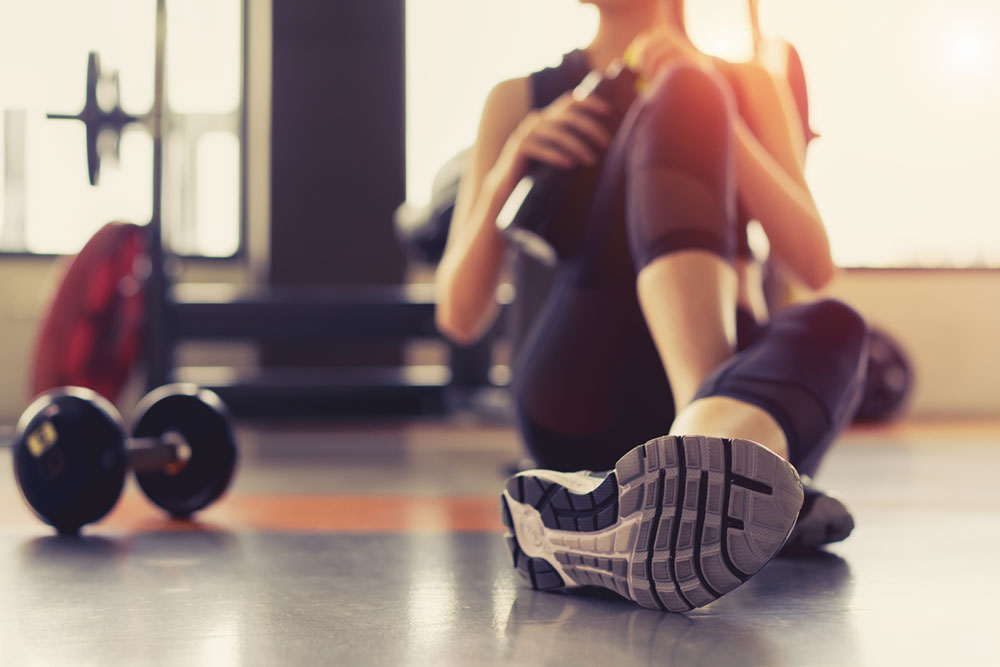 Female sitting on floor in the gym, one leg extended and blur image of dumbbell on floor next to her, water bottle in hand